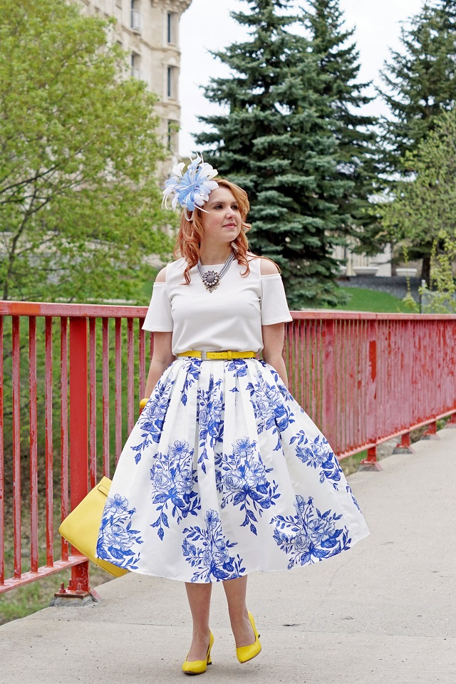 Winnipeg Canadian Fashion Consultant Stylist Blog, Chicwish blue delft china floral sketch pleated midi skirt, RW & co. open shoulder white blouse top, Danier leather Chloe saffiano leather satchel bag, Jacques Vert blue white feather fascinator hat, Heidi Daus flower necklace, John Fluevog yellow linen Big Presence Desmond pumps shoes