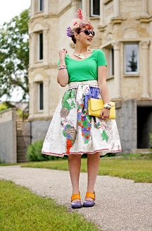 Everyday Outfit for July 24, 2013, Jay Manuel green scalloped t shirt top, Roobys skirts world map country print colorful full 50's circle skirt, BCBG white scalloped waist cutout belt, Danier leather yellow clutch bag, Jacques Vert silk flower feather white red purple fascinator, Ardene purple hair flower clip, Wayne Clark silver callalily choker necklace, Avon purple orange enamel bangles, Joan River white enamel bangle, Green Malachite silver gemstone ring, Diesel white silver cuff watch, Icing heart earrings, Shopcalico purple hart sunglasses, Fluevog Mini Zaza purple orange leather hourglass heels pumps